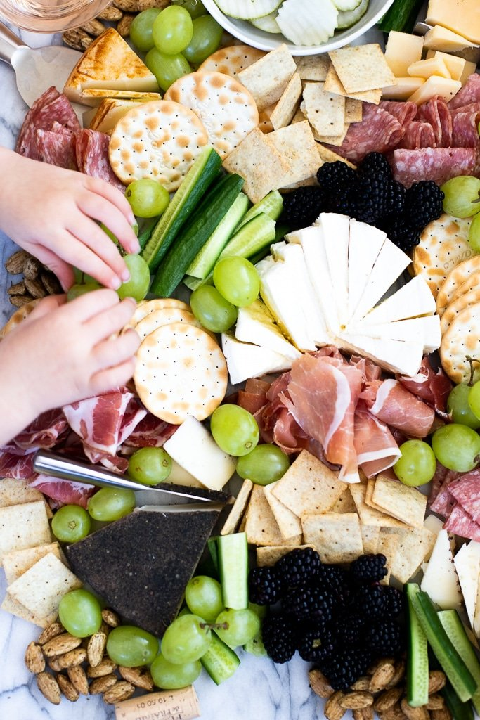 Overhead view of Costco cheese platter with hands grabbing
