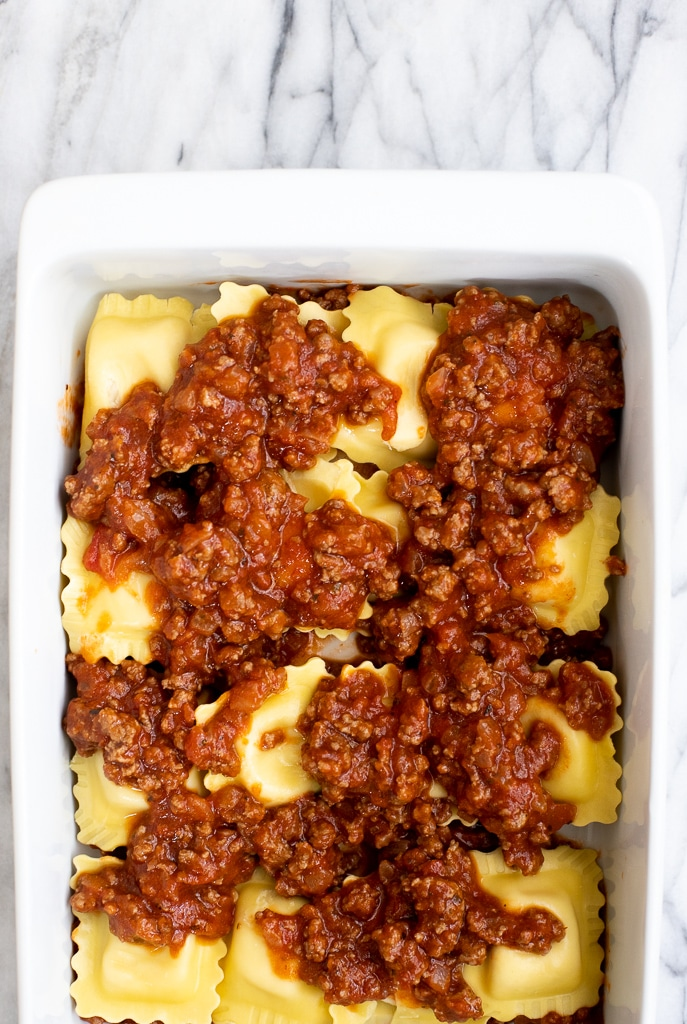 Layers of ravioli with ground beef in baking dish