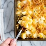 cheesy potato casserole in baking pan with a spoon