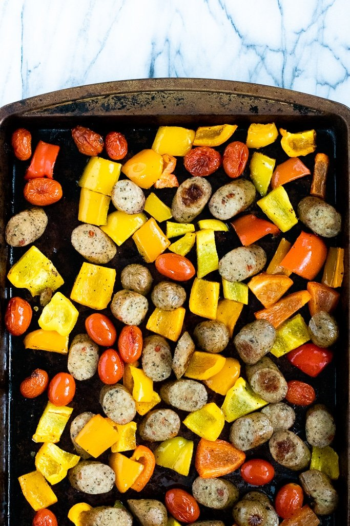 roasted peppers, chicken sausage, and tomatoes on a sheet pan