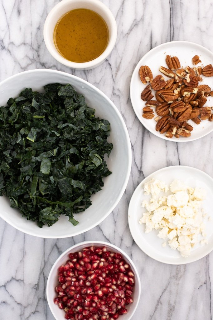 ingredients to make kale pomegranate salad recipe in white dishes