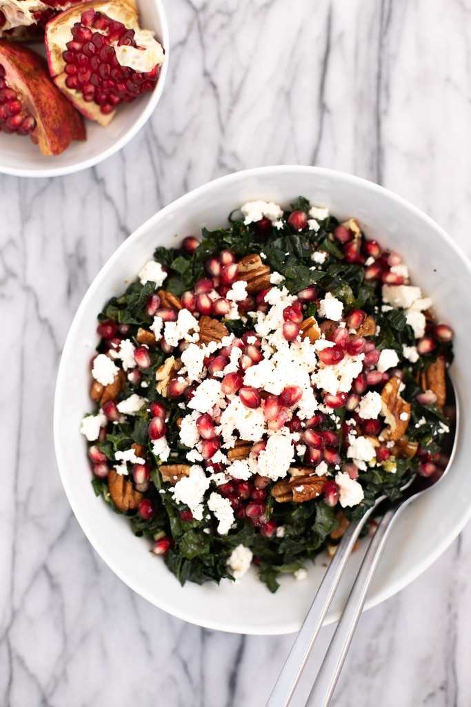 Kale pomegranate salad with feta in a white bowl