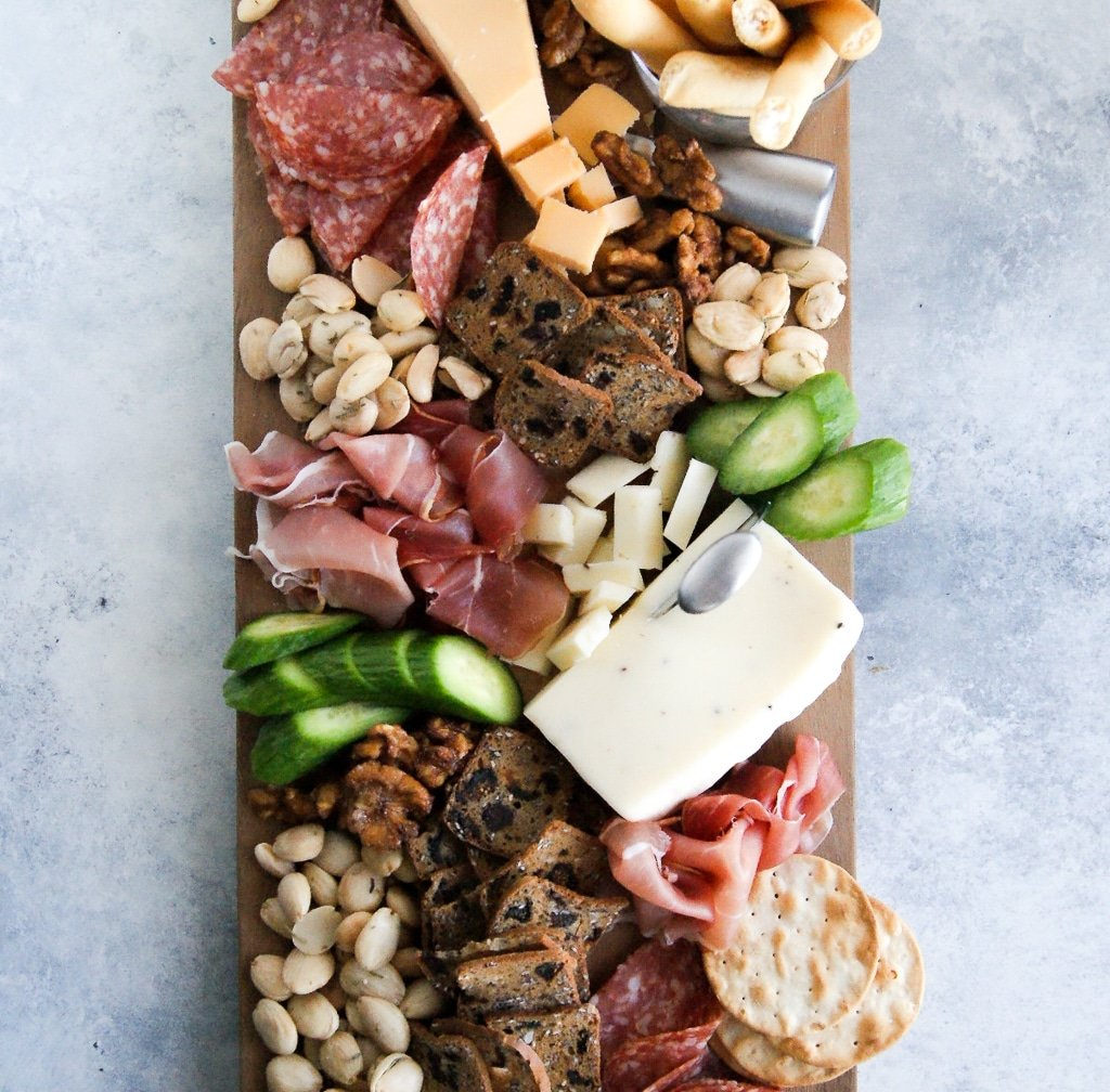 Trader Joe's charcuterie board with cheese, meat, nuts, crackers, and cucumbers