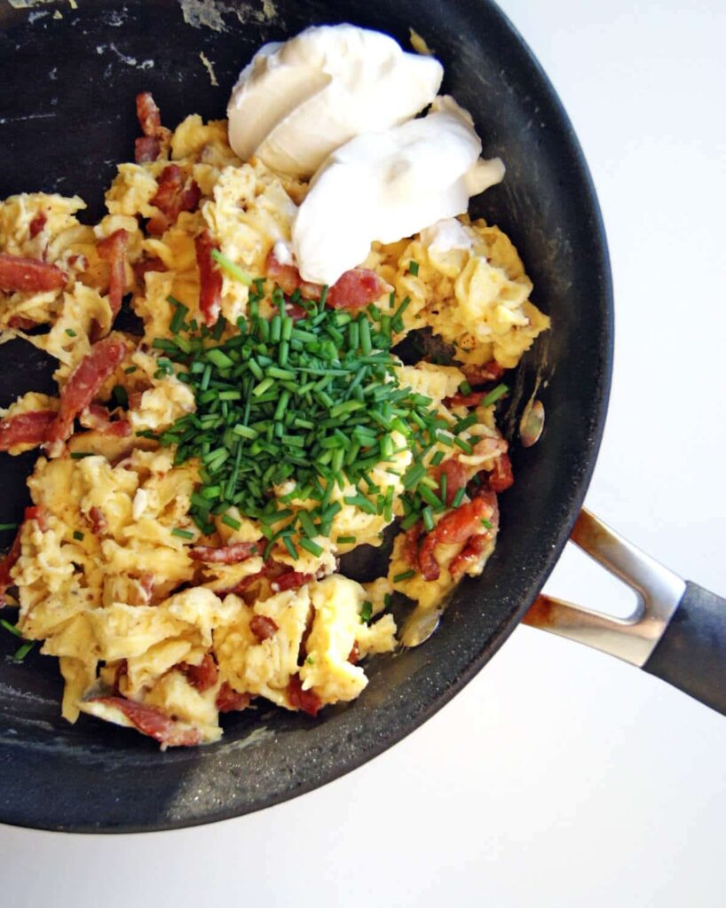 Eggs and sour cream in a skillet with chives