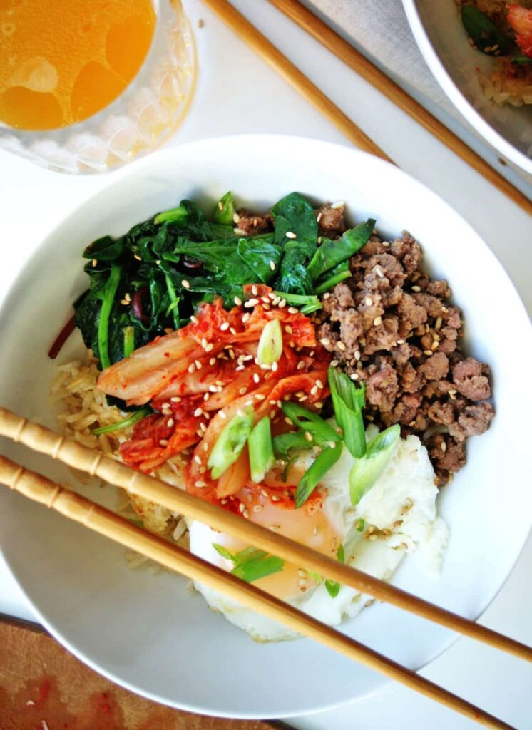 Easy Bibimbap Bowls   loaded with flavor: crispy rice, tasty ground beef, pungent kimchee and luscious fried eggs!