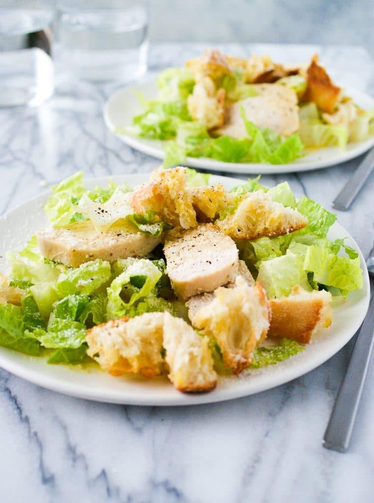 two plates of caesar panzanella salad