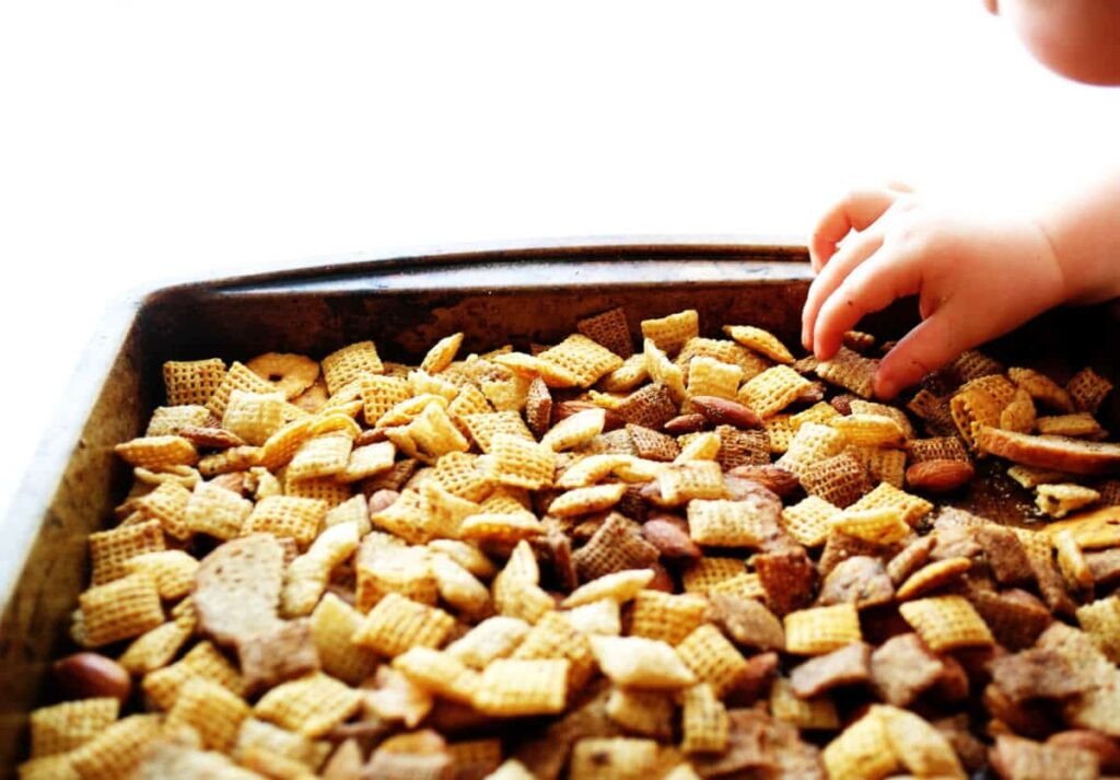 Tray of ranch chex mix with baby hand