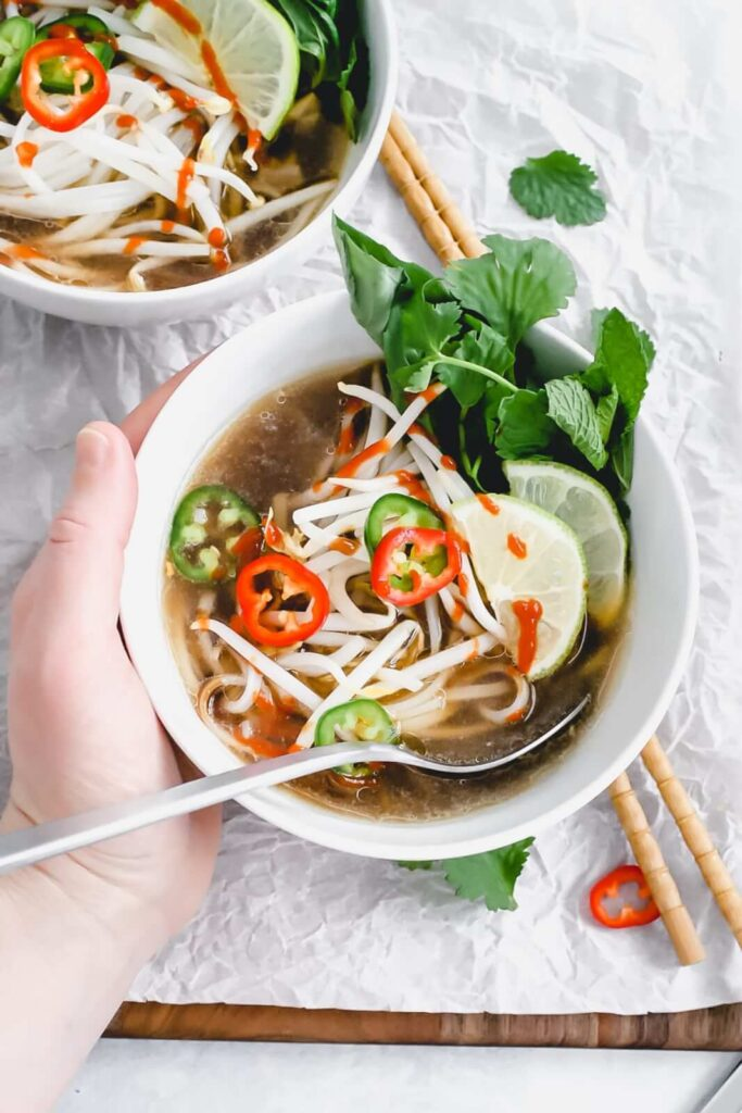 chicken pho in bowl with hand