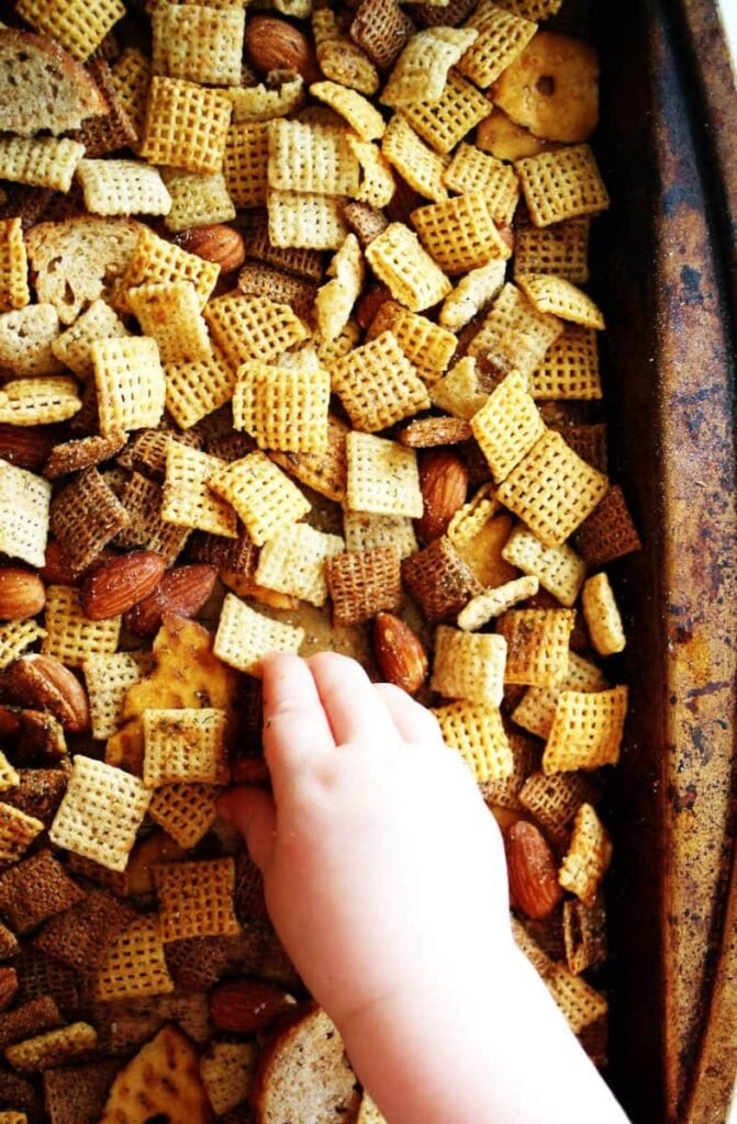 Sheet pan with ranch chex mix and baby hand grabbing