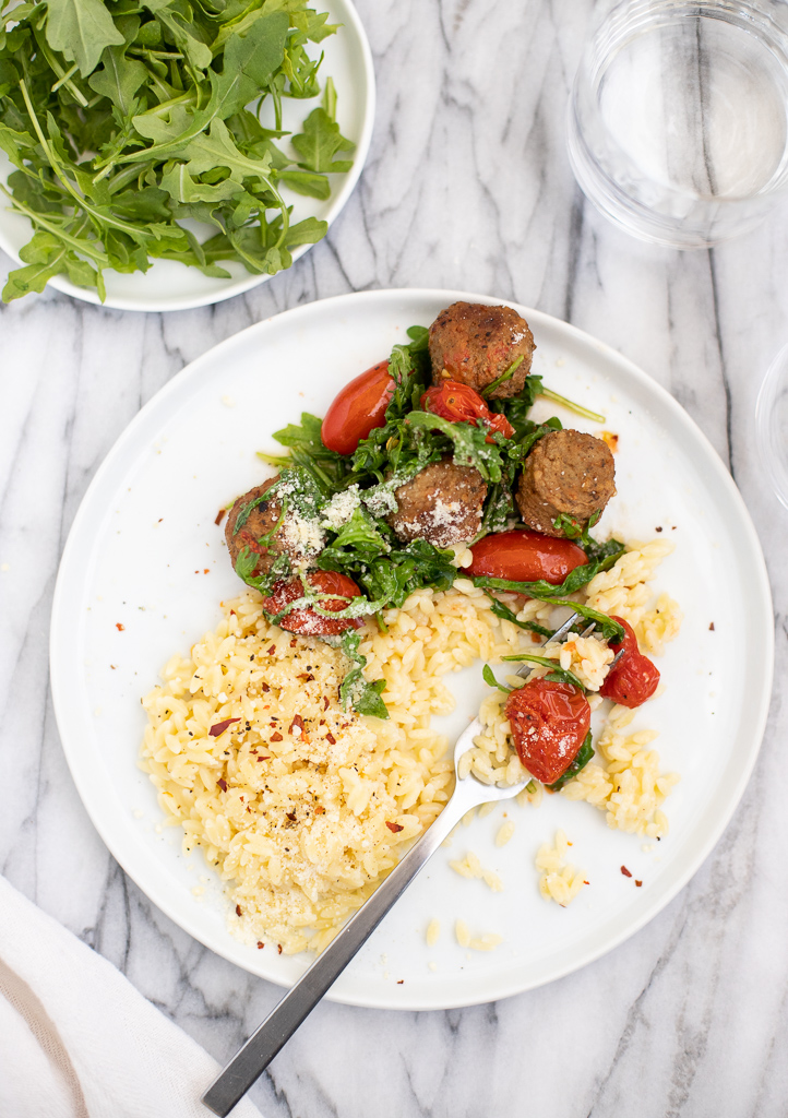 One plate of roasted meatballs tomatoes and arugula with orzo