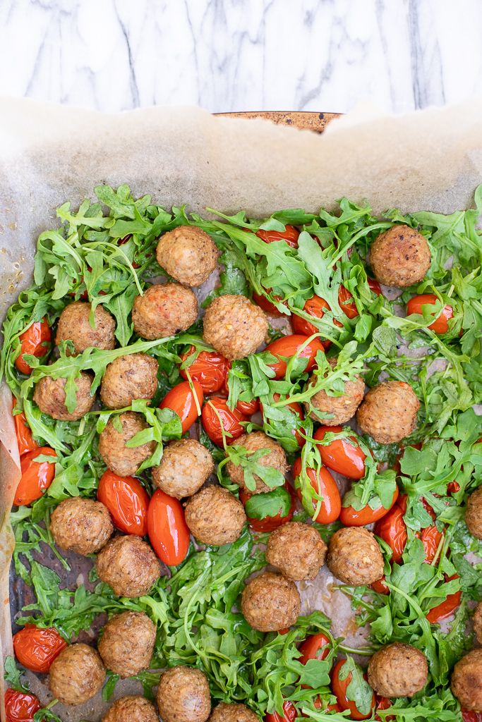 Sheet pan with roasted meatballs, tomatoes, and arugula