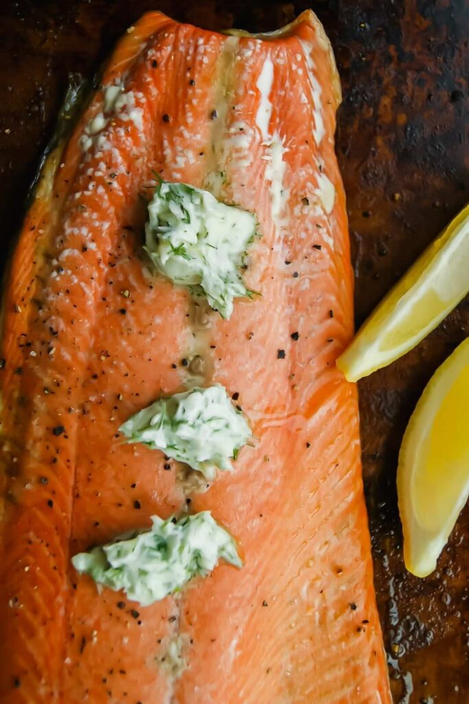 Salmon with dill butter sauce with lemon wedges