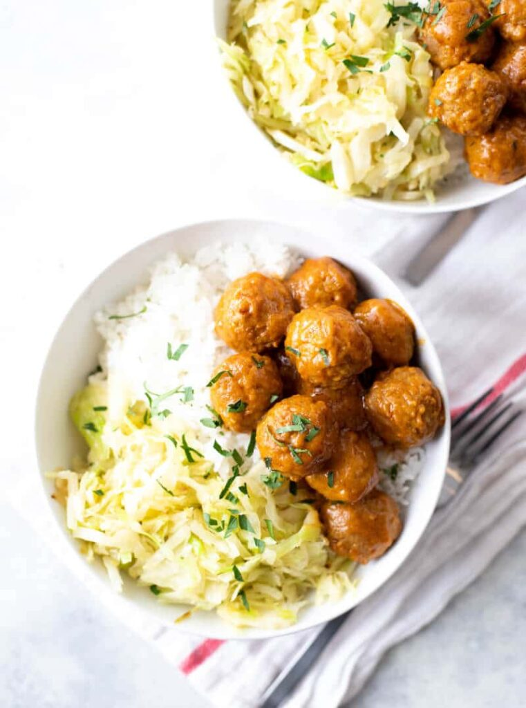 Trader Joe's curried meatballs in a bowl with rice and sauteed cabbage